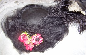 The finished hat, with three red peonies attached slightly to the left of the point where the tulle was attached.