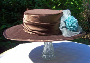 The brown velveteen Edwardian hat, with brown satin trim and blue flowers