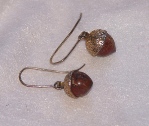 The silver-gilt acorn earrings.